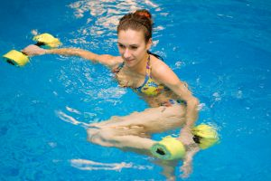 Woman in action in aqua aerobics with dumbbells